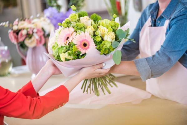 cropped-shot-of-florist-giving-beautiful-flower-bo-HKS8JMH